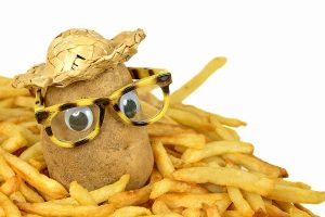 potato with straw hat and glasses in a pile of golden french fries. Use uniqueness for team success.